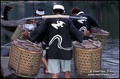 Japanese fishermen loading fishing boat with cormorants in bamboo baskets shortly before Ukai, traditional Cormorant Fishing, Iwakuni, Japan by Frantisek Staud