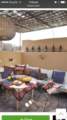 Spanish rooftop terrace with small Moroccan lanterns, built in benches, and colorful cushions