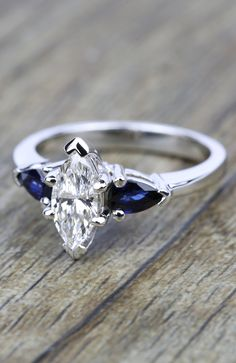 Two perfectly matched pear cut sapphire gemstones are prong set in this palladium gemstone engagement ring setting, accenting this marquise center diamond!