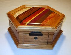 """Woods of the World"" - Jewlery box, Mahogany box with Cherry trimmed top and bottom and Ebony round inlays. Woods in the top - Cherry, Ambrosia Maple, King wood, Lacewood, Wenge, Padauk, Yellow Heart, Purple Heart, Black Walnut, Canarywood and Mahogany. Tony Williams"