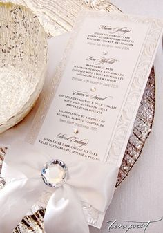 Elegant formal dinner menu for the wedding reception, embellished with a big satin bow with a crystal accent | WedAZ.com