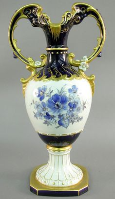 Czechoslovakia ~ Royal Dux ~ Double handled urn ~ Stting on a footed pedestal ~ It has a blue floral decoration trim and gilt adornments ~ Circa 1901-1930