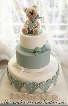 Tiered baby shower cake with bear topper                                                                                                                                                     More