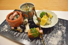 Rikyo in Osaka - Bricolage of flavor: A selection of salads accompanied by a sprig of cherry blossom — a hint of the warm weather to come.