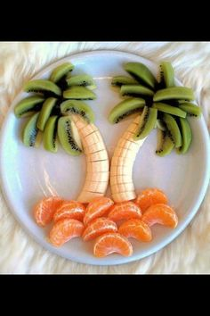 Good snack! It is bananas for the trunk, kiwi for the palm tree leaves, and mandrain oranges for the ground!