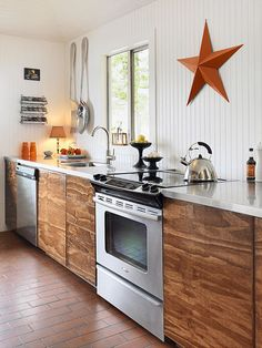 Wood and white contrast in the new kitchen: Fir plywood cabinets echo the cedar ceiling, while white appears in the stainless steel countertops and tongue and groove paneling. The lack of upper cabinets opens up the space.