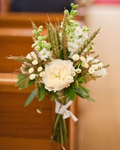 Wild posies of ruffled heirloom roses, stock, and japonica in soft white tones were tied to the ends of the church pews with cotton grosgrain ribbon