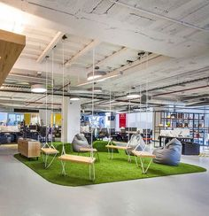 This Red Bull Office has a casual meeting area with a green rug and swings.