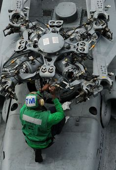 A Sailor assigned to Helicopter Maritime Attack Squadron (HSM) 70 performs maintenance on an MH-60R Sea Hawk helicopter aboard the aircraft carrier USS George H.W. Bush (CVN 77).