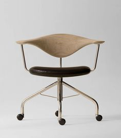 """HANS WEGNER // """"Swivel Chair"""" During a Danish furniture trade show, Dr. Eigill Snorrason critiqued the industry for not paying enough attention to ergonomics. The Swivel Chair (1955) Wegner's rejoinder of sorts, an elegant backrest of hand-carved wood that's been compared to a gently bent propeller. The smooth lines, thin profile and wheels invite a sure-footed slide across any office. Manufactured by PP Møbler. Photo by Jens Mourits Sørensen."""