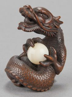 Wood netsuke of roaring dragon holding ball, carved by Kaigyokudo, Osaka, circa 1833-1843, signed by artist.