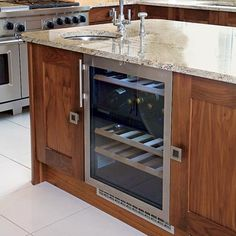 a kitchen island with a cooling unit for wine storage