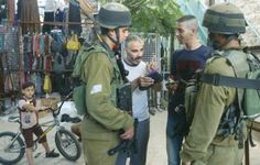 IDF soldiers speak with Palestinians in Hebron last week during the manhunt for three kidnapped Israeli youth.