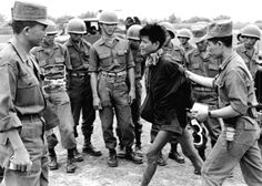 A Viet Cong POW is marched past ARVN troops, 1962.