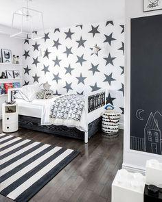 Графическая черно-белая комната для мальчика дошкольного возраста. Черные звезды на белом фоне одной из стен комнаты в сочетании с меловой доской на другой стене – оригинальное и функциональное оформление стен детской