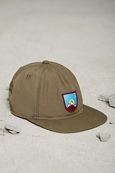 198eb450b00c A nylon snapback hat featuring a mountain patch on the front and an  adjustable snap back