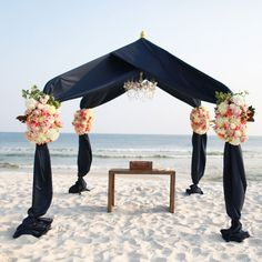 BEACH WEDDING: A frame draped in navy fabric and accented with large bouquets of pink and white flowers made for a stunning beach ceremony