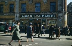 Women are pictured crossing the street in front of a family butchers shop in Moscow's Arba...