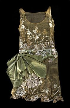 Pale green short beaded and embroidered dress with bow detail    Number: BATMC I.09.97  Material(s): silk, glass and synthetic  Technique(s): woven (chiffon), woven (velvet) and applied (beads)  Creation date: 1926