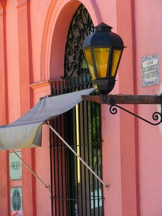 In Uruguay...love the color, lantern, awning, arch over door and gate/door!