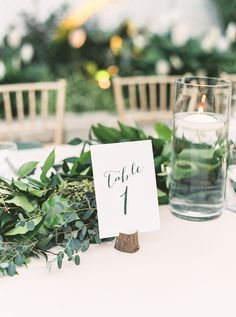 Round tables were decorated with high and low centerpieces, all filled with dark foliage, larkspur branches, and a mix of peonies, garden roses, lisianthus, and sweet peas. Simple black and white number cards marked each table.