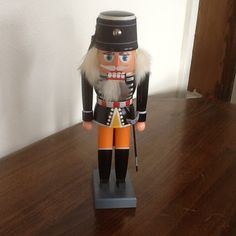 Special detail goes to his Black coat with all the designs and his orange pants. His sword is at his side. His blue hat has a metal emblem on the front. He stands 10 tall and is from West Germany Orange Pants, Nutcrackers, Sword, Germany, Hat, Detail, Blue, Vintage, Design
