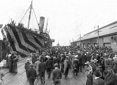Crowds on a wharf at Outer Harbour, South Australia, welcoming camouflaged troop ships bringing men home from service overseas, circa 1918. (State Library of South Australia)