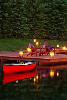a red canoe - at a dock with chairs surrounded by glowing lanturns