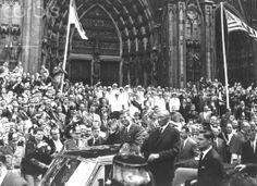 1963. 23 Juin. Cologne. President John F. Kennedy (m, waving) and Federal Chancellor Konrad Adenauer (m, standing) drive in an opentop car through Cologne past an enthusiatic crowd of people, in June 1963, during Kennedy's visit in Germany. Cologne Cathedral in the background