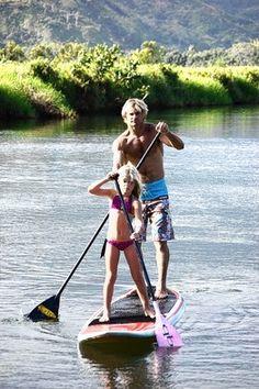Surfer Laird Hamilton, with daughter Reece, 6, on Hanalei River, Kauai.