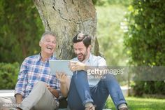 Stock Photo : Father and son using digital tablet outdoors
