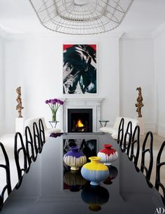 In the same home, a Fredrikson Stallard light fixture hangs over the first-floor dining table, which is topped with a trio of Ai Weiwei vases and lined with Bonetti chairs   archdigest.com