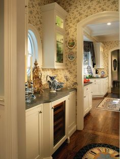 The butler's pantry opens into the kitchen and dining room through two graceful archways. A glass-faced wine refrigerator can service both the kitchen and dining rooms.
