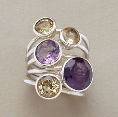 citrine & amethyst cluster rings. Five faceted beauties, three citrines and two amethysts, cluster on the finger atop sterling silver bands. Held together with sterling silver band.