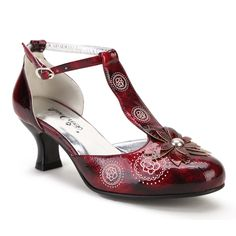 This red leatherette pump is constructed with a supportive arch area as well as padded insoles, and comes with matching heel covers. The style features a stud centered leaf flower on front upper, and embellish imprint details over the vamp.