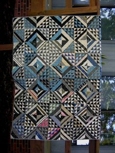 Mid to late 1800's hand sewn quilt, period fabrics, predominantly blue, black and white. Fancy four-patch pattern: strip piecing alternates with half-square triangles.