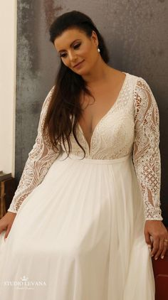 81976c5b3ae Bohemian plus size wedding gown with long lace sleeves and deep V cleavage.
