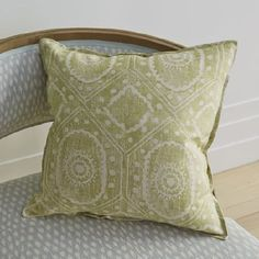 Blithfield -  Peggy Angus Fabric Collection - A green and white printed scatter cushion on a wooden framed armchairmade with a blue and white patterned seat and back