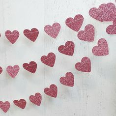 This paper garland measures ten (10) feet in length and is made as a single strand of hand punched hearts.    Colors:  Glitter Pink (one sided,