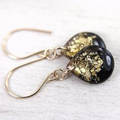 Teardrop earrings are filled with black glitter, gold flakes and glitter. They hang from hand formed 14 karat gold filled ear wires with rubber