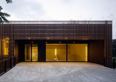 Internal lighting shines between the vertical larch battens that clad this extension to a primary school near Basel by Swiss firms Zwimpfer and BBK.