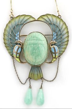A Egyptian revival plique-à-jour enamel and amazonite scarab pendant/brooch, circa 1920, with modern fourteen karat gold chain carved amazonite scarab flanked to either side with stylized peacocks, each with an outstretched wing and suspending an amazonite drop; mounted in silver.