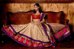 Beige and gold brocade lengha with a fuschia and purple border.