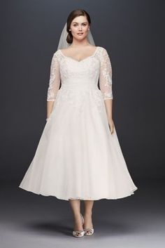 Designed exclusively for plus-size figures, this classic tea-length wedding dress flatters with beautiful details. The illusion sleeves are appliqued with embroidered lace blooms and finished with sca