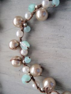 Hand knotted beige and white glass pearls and robin egg blue czech glass make this necklace a spring staple piece! The robin egg blue combined with the dark brown thread makes me think of baby bird eggs nestled in a little nest in a tree branch! Loop & button closure. Measures 18 1/2