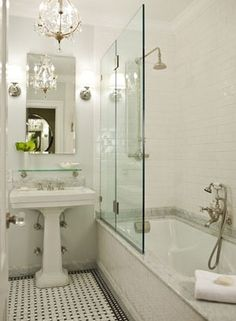 I love a lot about this.  Suzie: Morris Adjmi Architects - Stunning, elegant bathroom design with white pedestal sink, rectangular frameless mirror, Restoration hardware vintage glass shelf, soft gray walls paint color, marble basketweave tiles floor, subway tile shower surround, rain shower head and crystal chandelier.