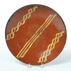 """Garth's Sale 1114 Lot 632. May 17 2014. REDWARE PIE PLATE.  American, mid 19th century. Coggled rim and yellow slip decoration. Wear. 10.75""""d.  Estimate $ 200-300."""