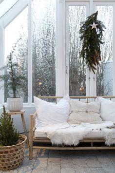Bambubänken från Tine K home med sköna kuddar och ett getskinn från Hemslöjden ger en välkomnande och mjuk känsla i växthuset.
