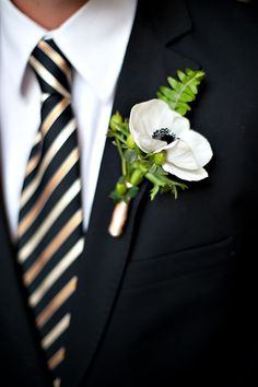 Gold boutonniere and a striped gold and black necktie