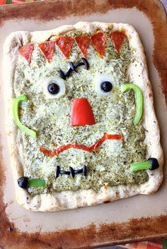 Frankenstein Pesto Pizza This Frankenstein Pesto Pizza is so charming that hes almost too cute to eatbut who can resist pizza? What a great way to get kids to eat their veggies! The post Frankenstein Pesto Pizza was featured on Fun Family Crafts. Halloween Pizza, Cute Halloween Treats, Halloween Punch, Halloween Dinner, Halloween Goodies, Halloween Crafts For Kids, Halloween Food For Party, Halloween Cupcakes, Spooky Halloween